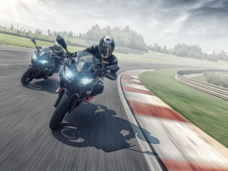 Two riders in formation on race track each on a 2019 Kawasaki Ninja® 400