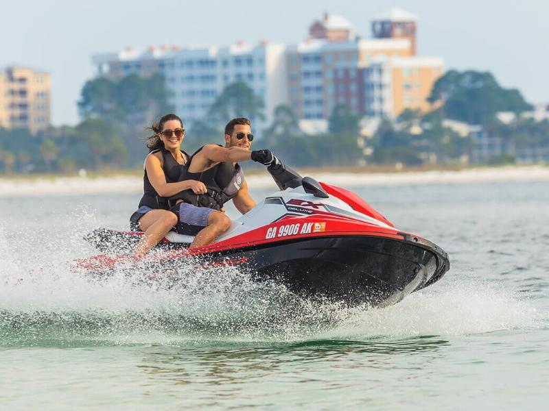 Man and woman riding a Yamaha WaveRunner® EX Deluxe off the coast of a city