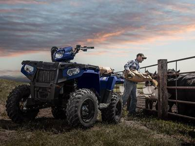 Polaris® utility atv in front of a fence and a man feeding his cattle