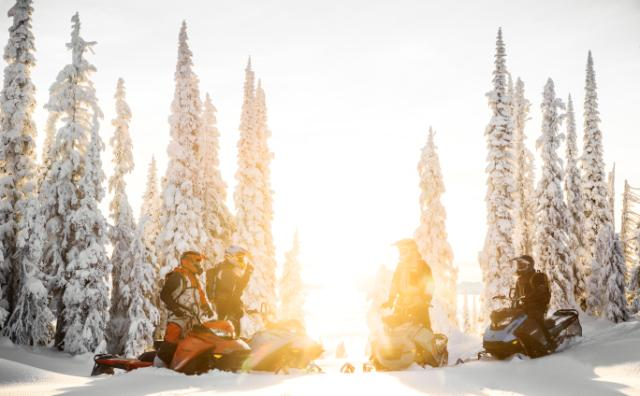 A group of snowmobiles hanging out in the snow