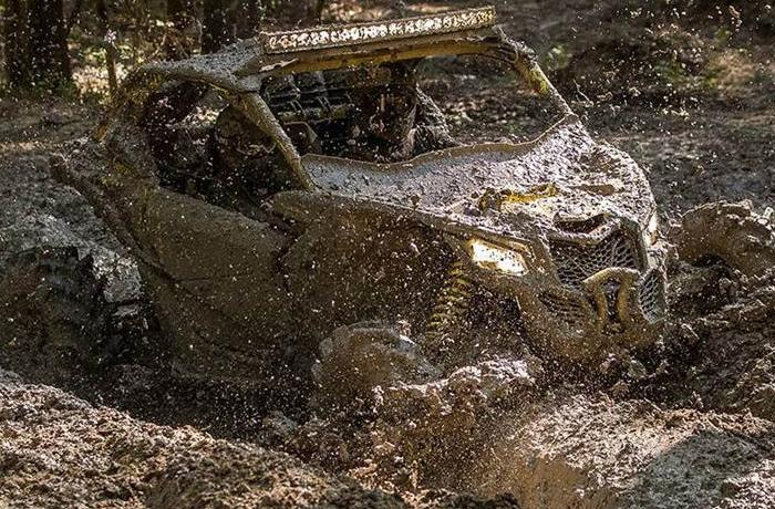 Can-Am SxS taking on a huge mud pit.