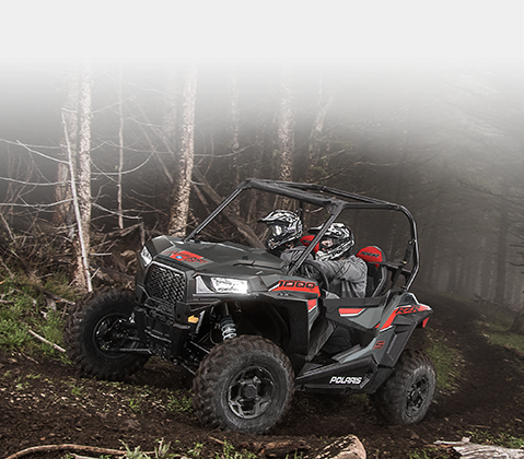 Riding in the woods on a misty trail on a Polaris® SxS