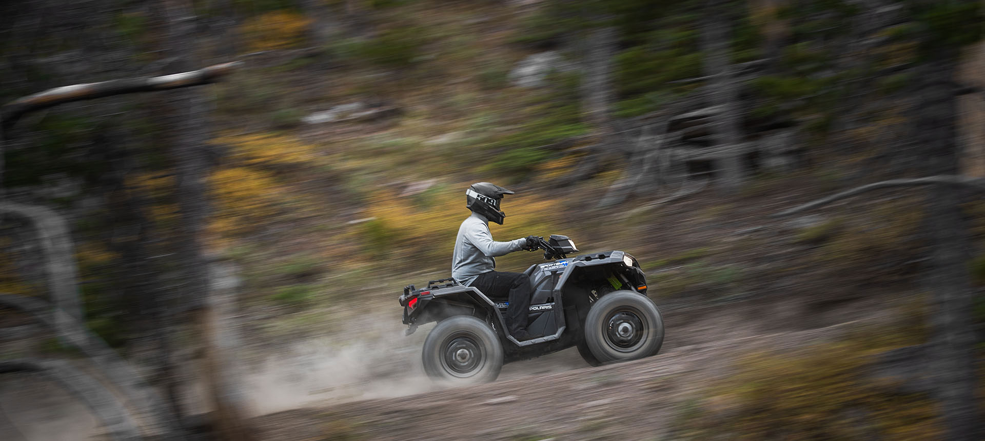 Racing along a trail in the woods on a Polaris® ATV