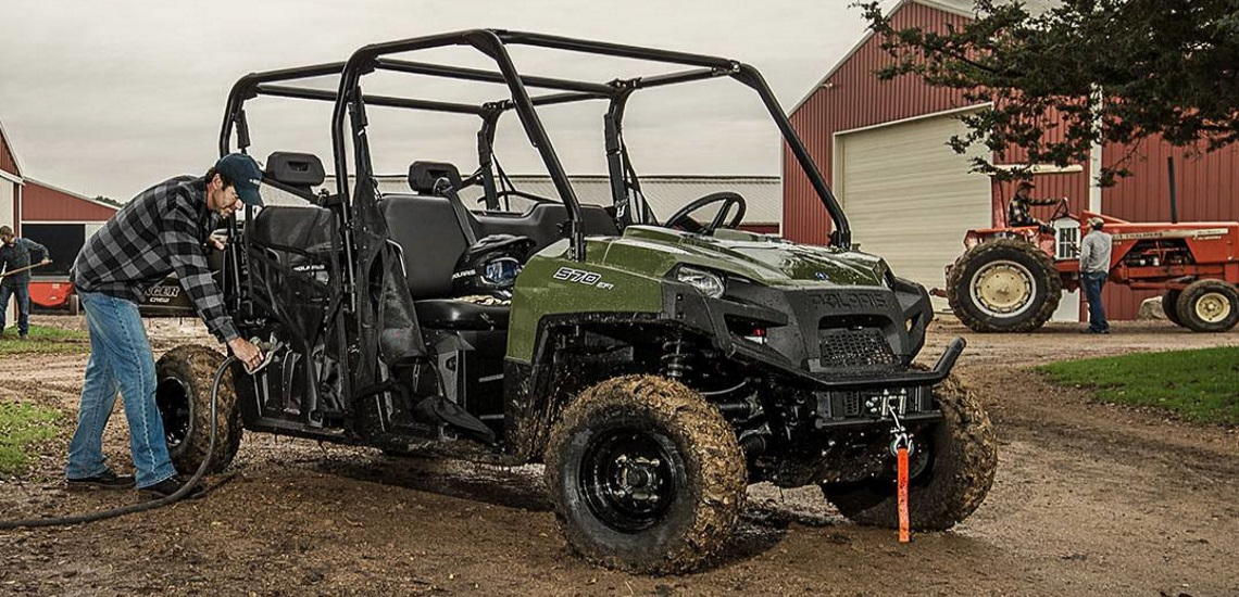 a person taking a moment to get fuel for his 2019 Polaris Industries Ranger Crew 570-6 in Sage Green