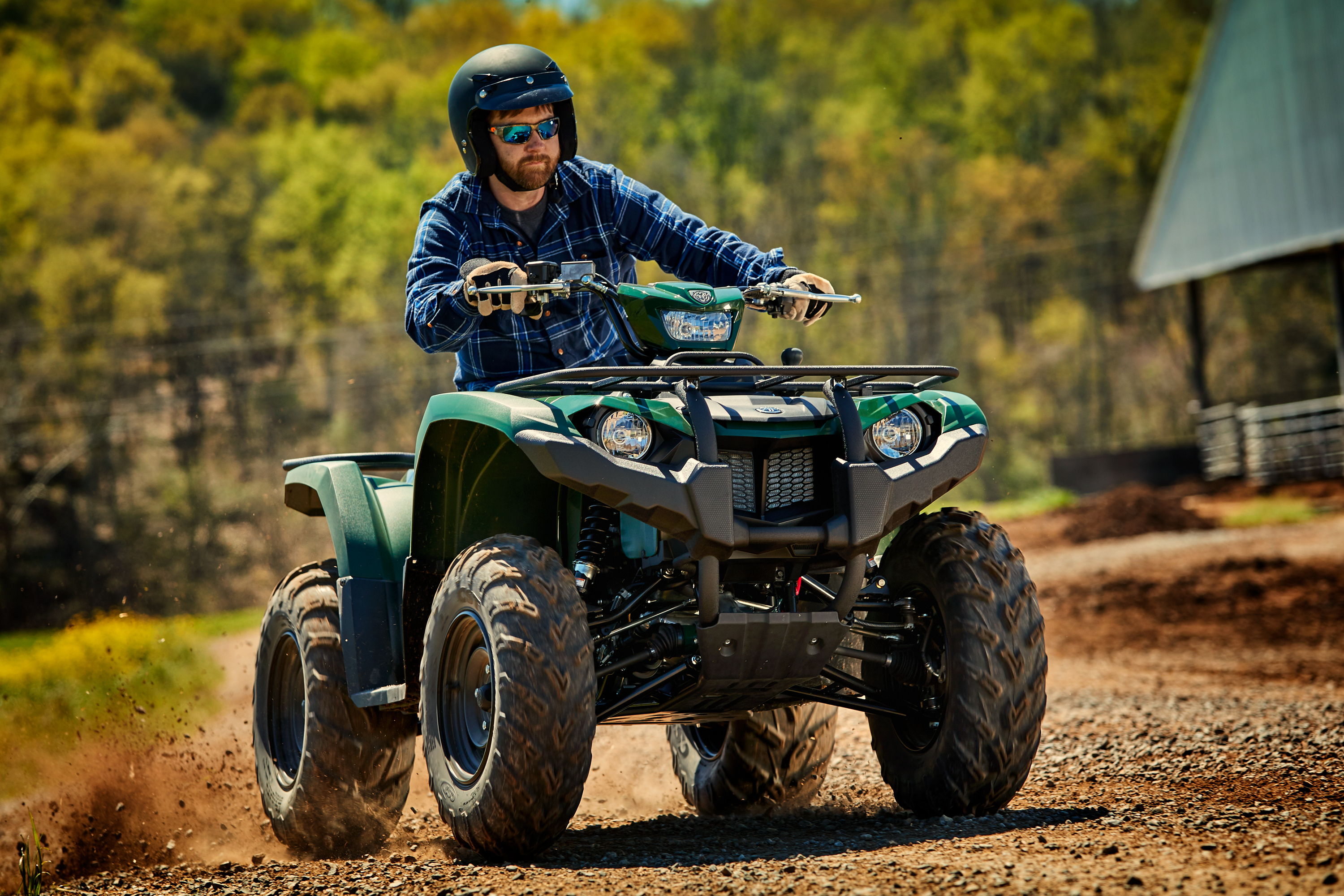 Man riding on a green Yamaha ATV with sunglasses