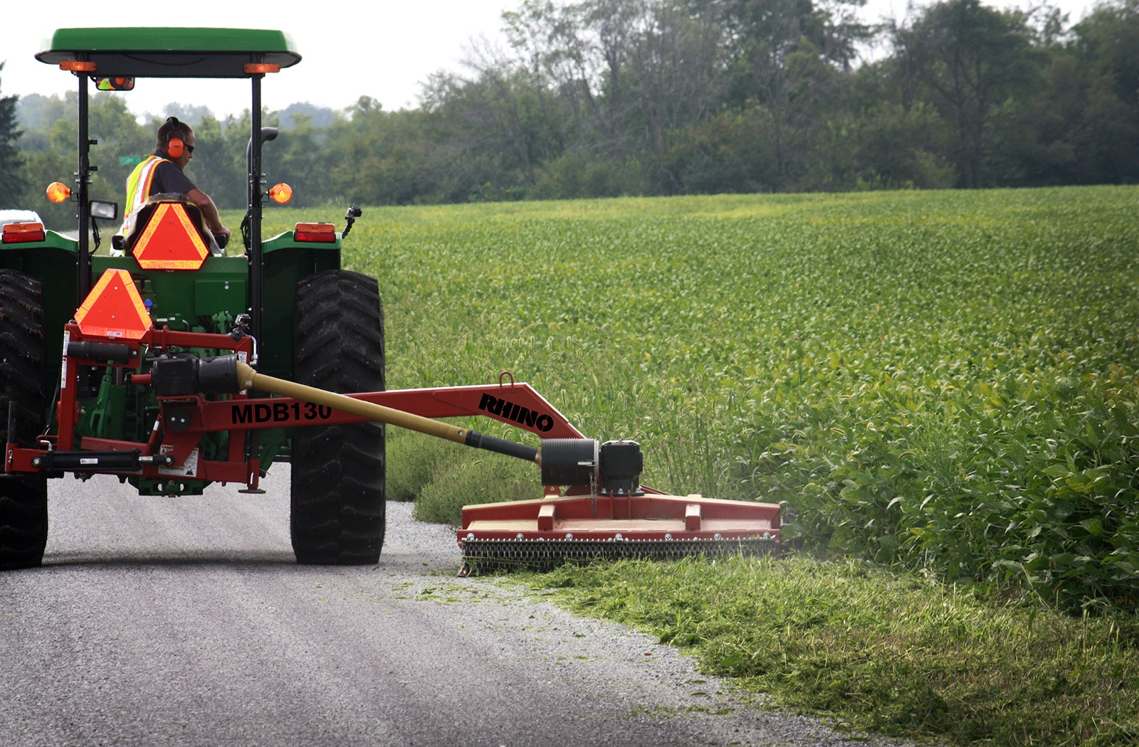 Ag mower cutting grass and plants on the side of the road