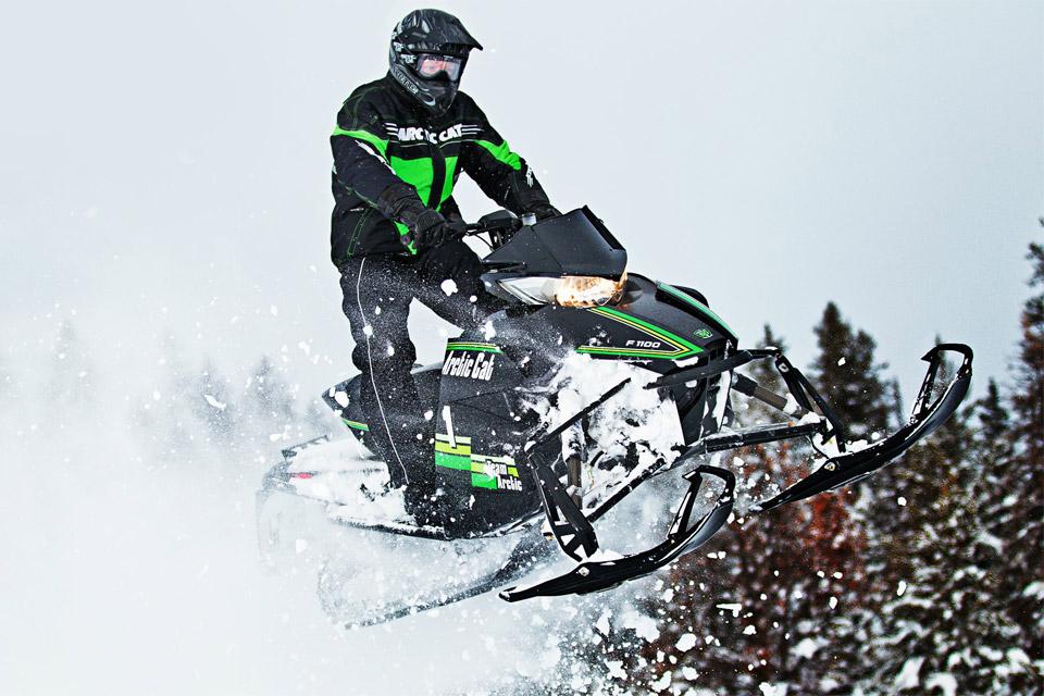 Man jumping an Arctic Cat Snowmobile