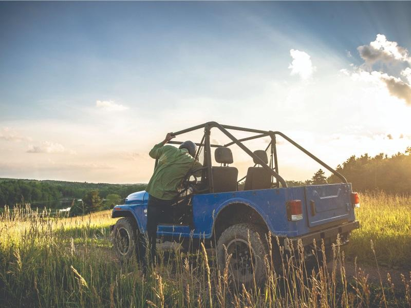 Man getting into a 2019 Mahindra ROXOR Classic in a field of wheat