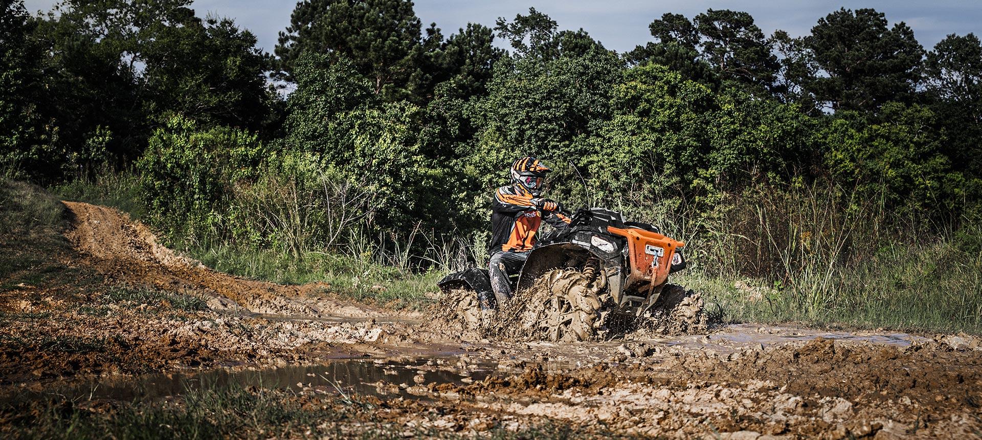 Polaris ATV taking on a muddy crossing.