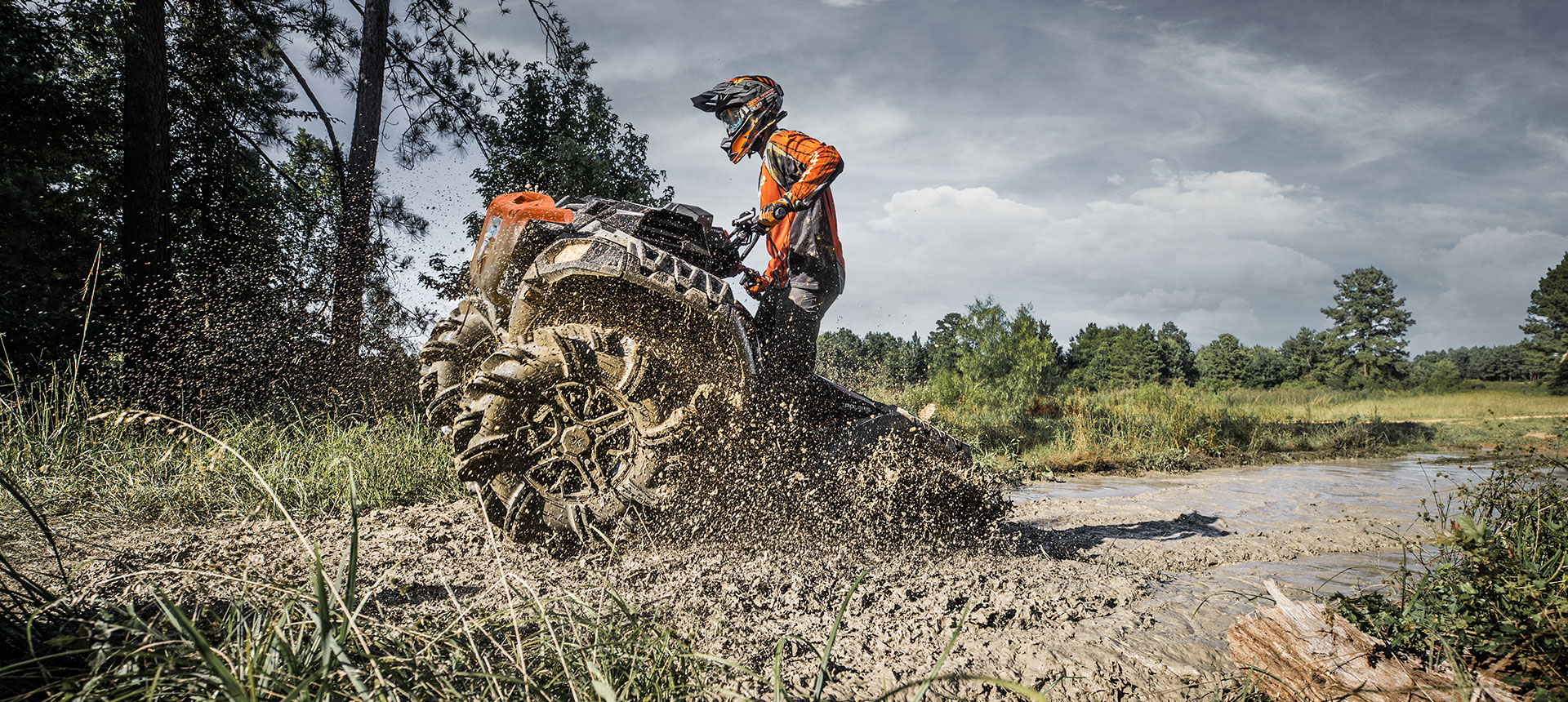 Polaris ATV coming out of a huge mud filled hole.