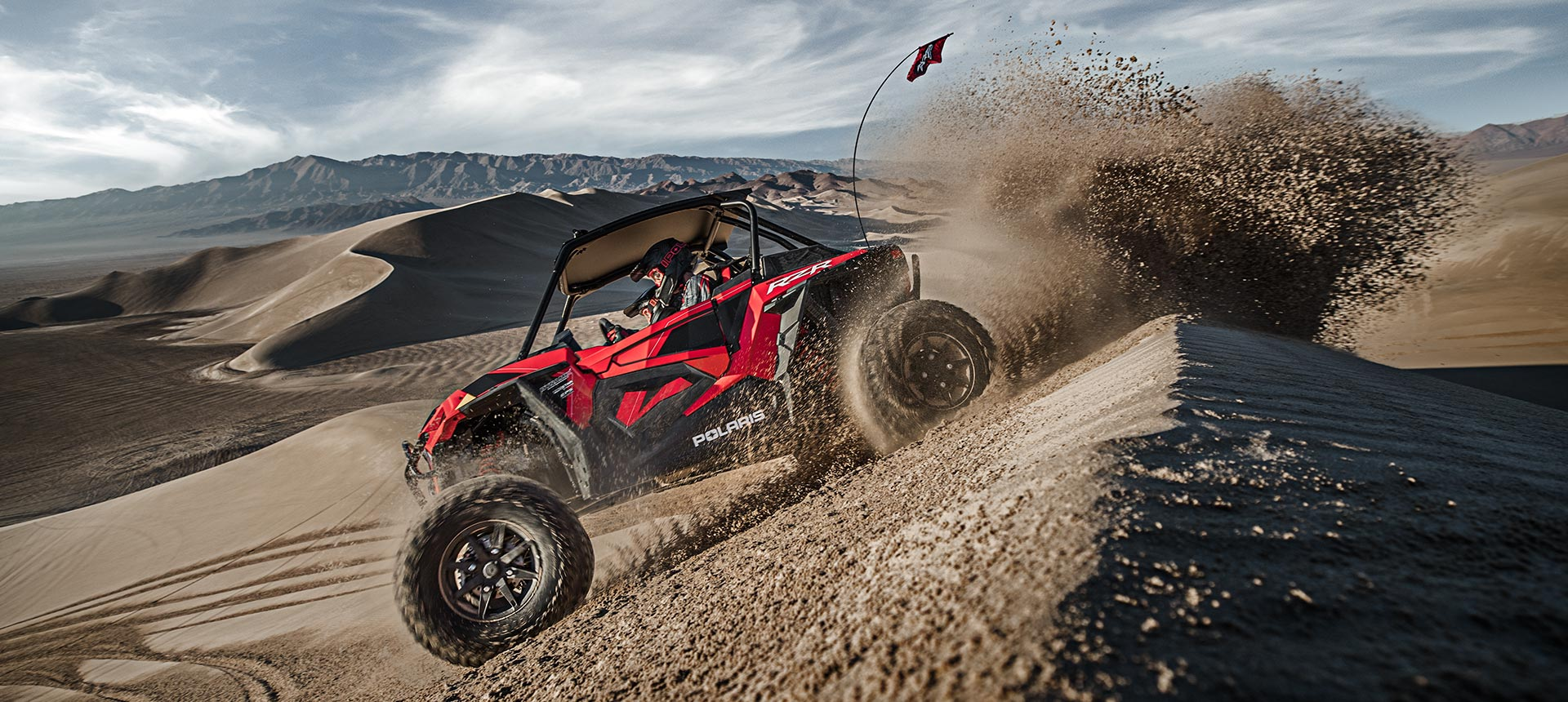 Polaris RZR going over a sand dune