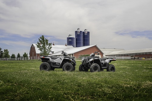 Polaris ATVs idle in a field