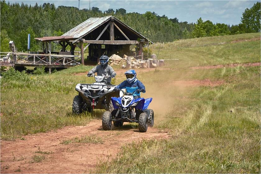 Two people on Yamaha Raptor ATVs on a dirt trail.