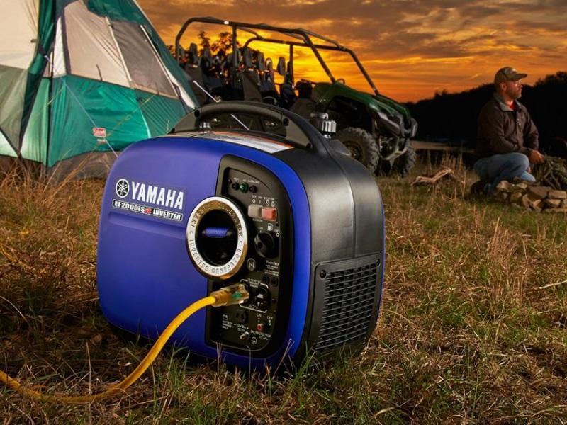 Camper admires the twilight sky as a Yamaha EF2000isV2 inverter generator powers an off camera light