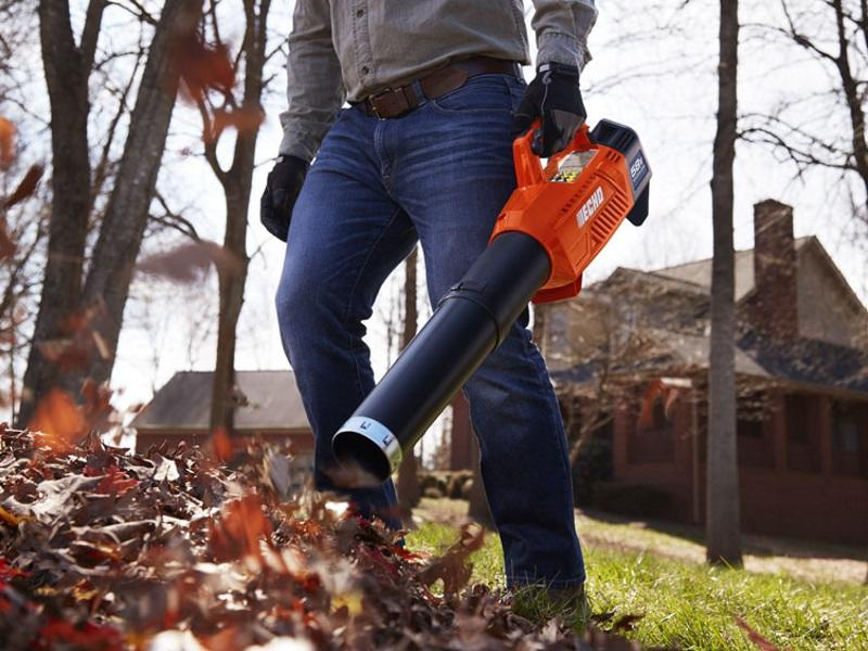 Man using an ECHO handheld blower to blow leaves from his property