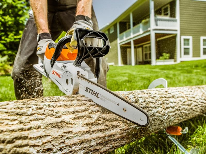 Man using a STIHL® chainsaw to cut a tree