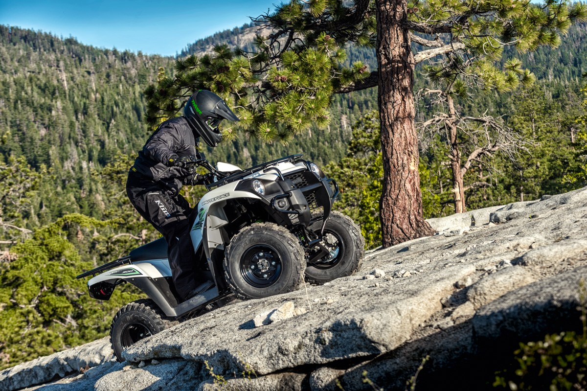Manuvering over a rock crest on an atv.