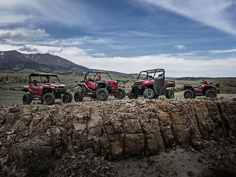 Line up of Polaris® powersports vehicles overlooking a cliff.