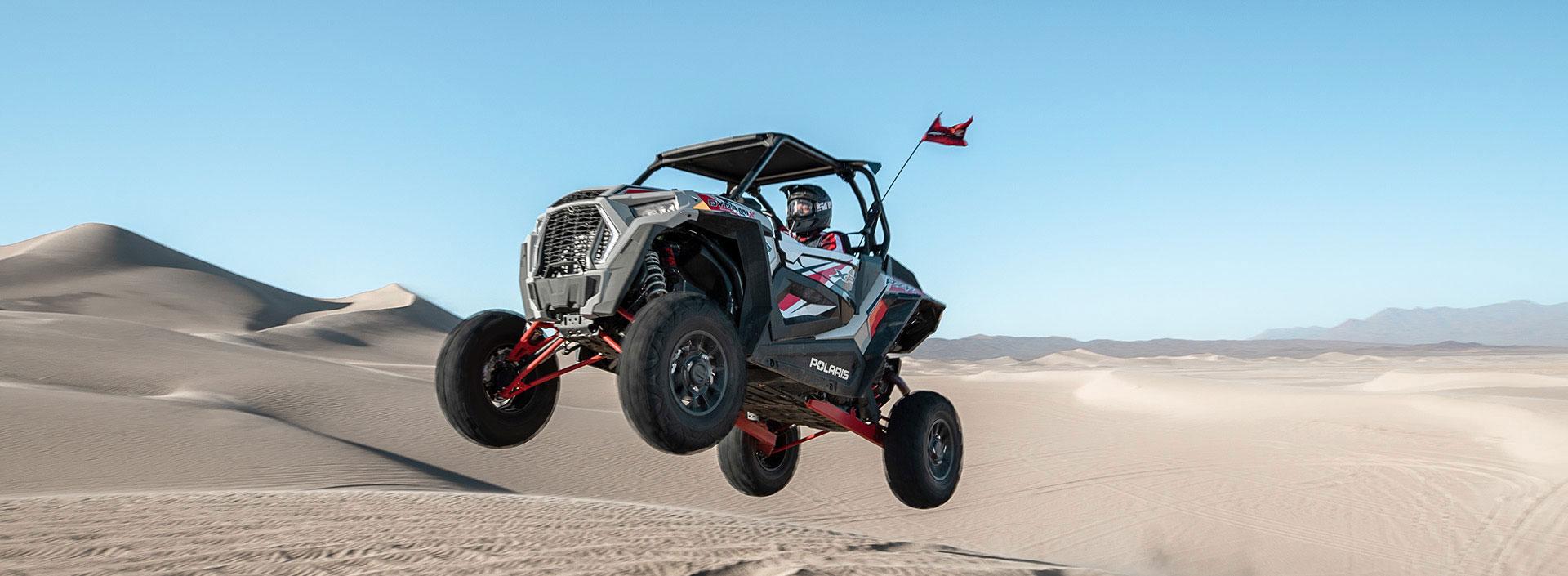 Polaris® RZR jumping over a sand dune.