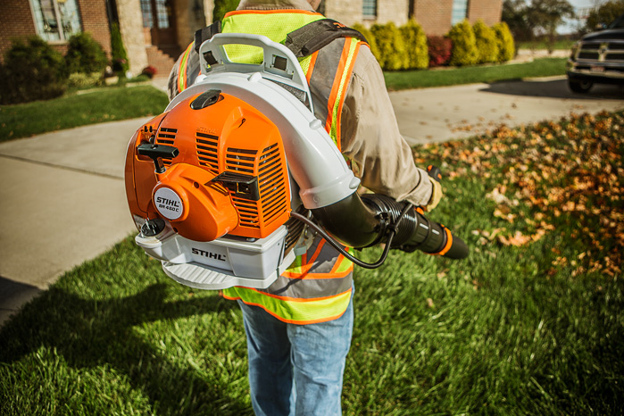 Man uses a STIHL® blower to clear the leaves in a yard.