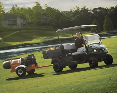 Man tows equipment across a golf course with a Cushman utility vehicle.