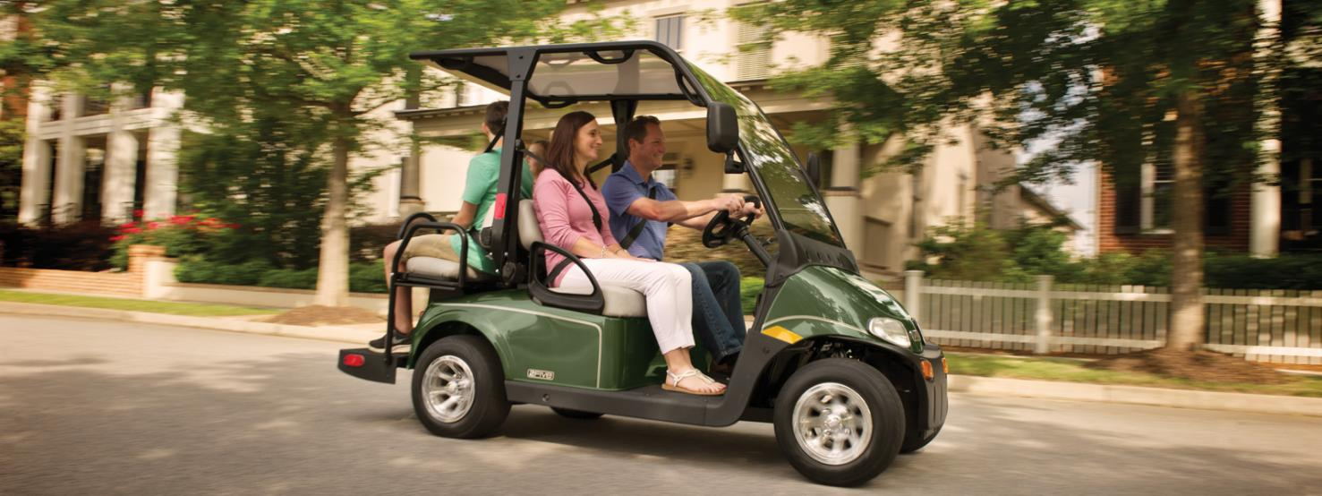 family riding 4-seater E-Z-GO gas powered car