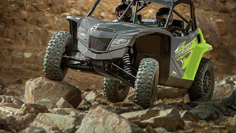 Two people in a Textron Off Road Wildcat XX side by side riding over rough terrain.
