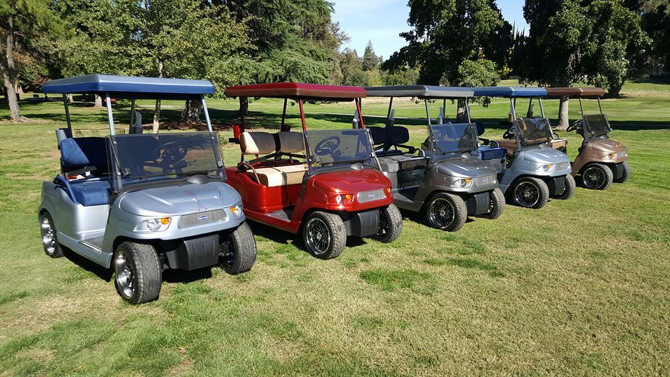 Five Western golf cars lined up on a golf course.