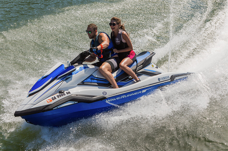 Two people on a Yamaha WaveRunner® making turns on the water.