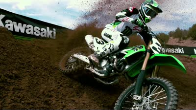 Kawasaki dirt bike ripping up a corner on a track