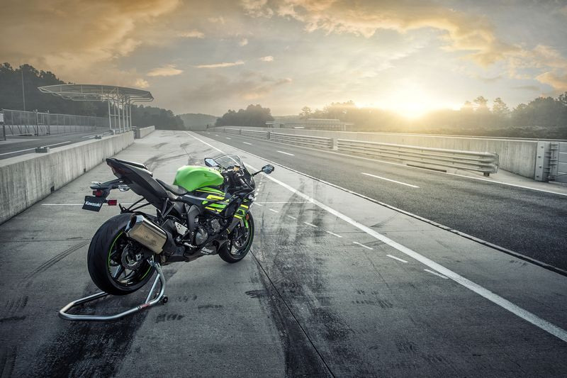 Kawasaki superbike parked at a track at sunset