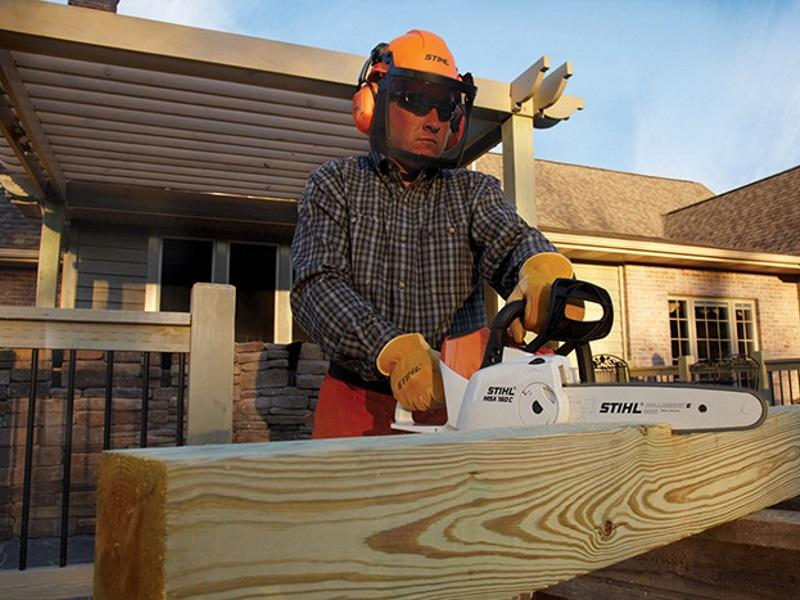 Man using a STIHL chainsaw to cut wood for his new house he's building