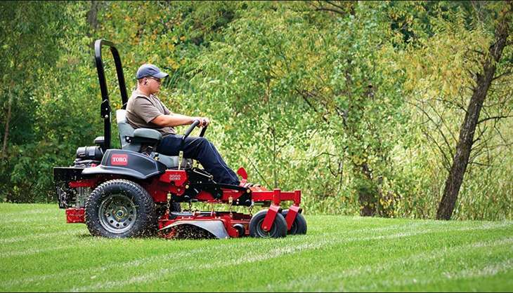 Man on a Toro® riding mower cutting the grass with some grass clippings blowing around him in the wind.