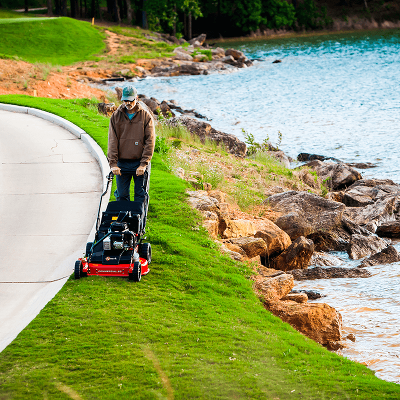 Mowing grass with an eXmark walk-behind mower.