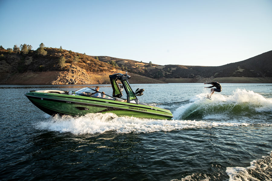 Man water-skis off the back of a green Centurion boat.