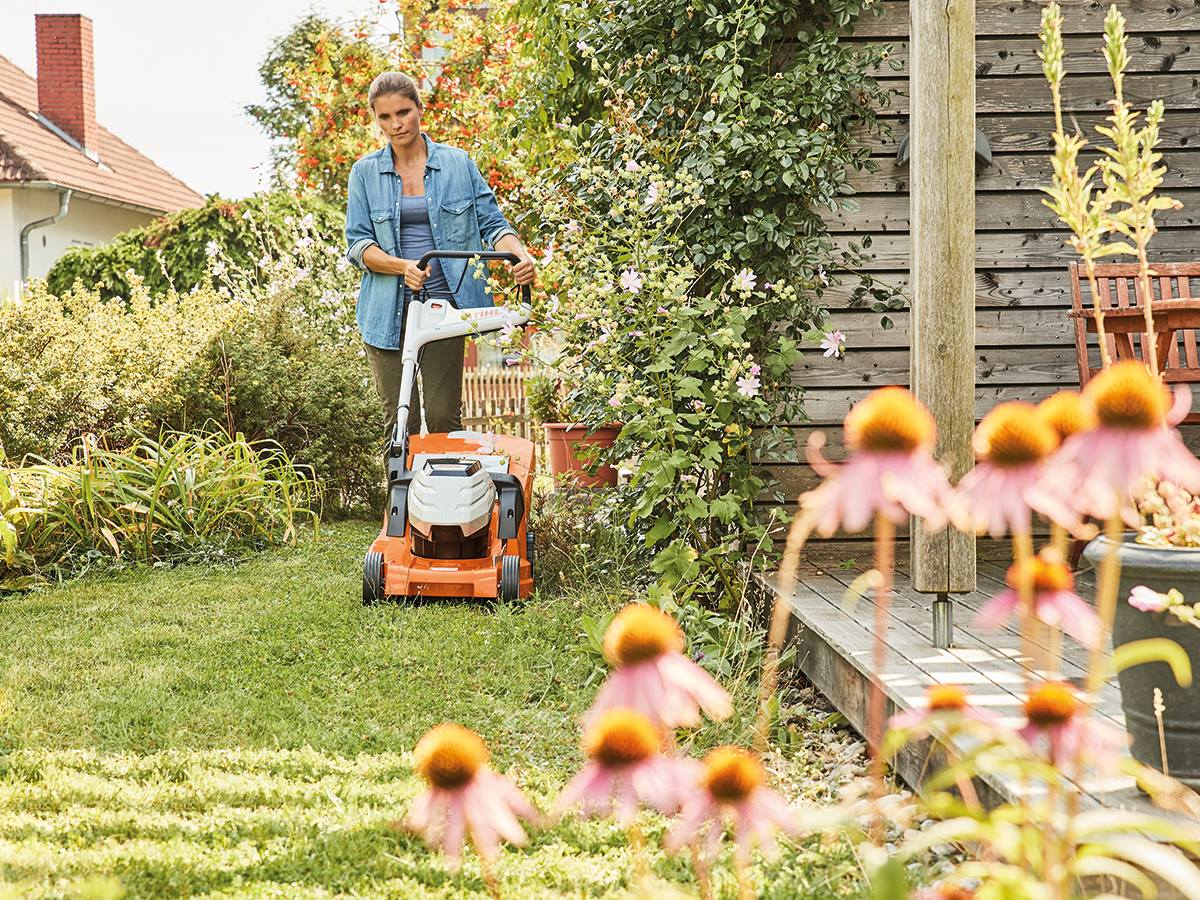 A woman uses a STIHL® lawn mower to cut the grass in her backyard.