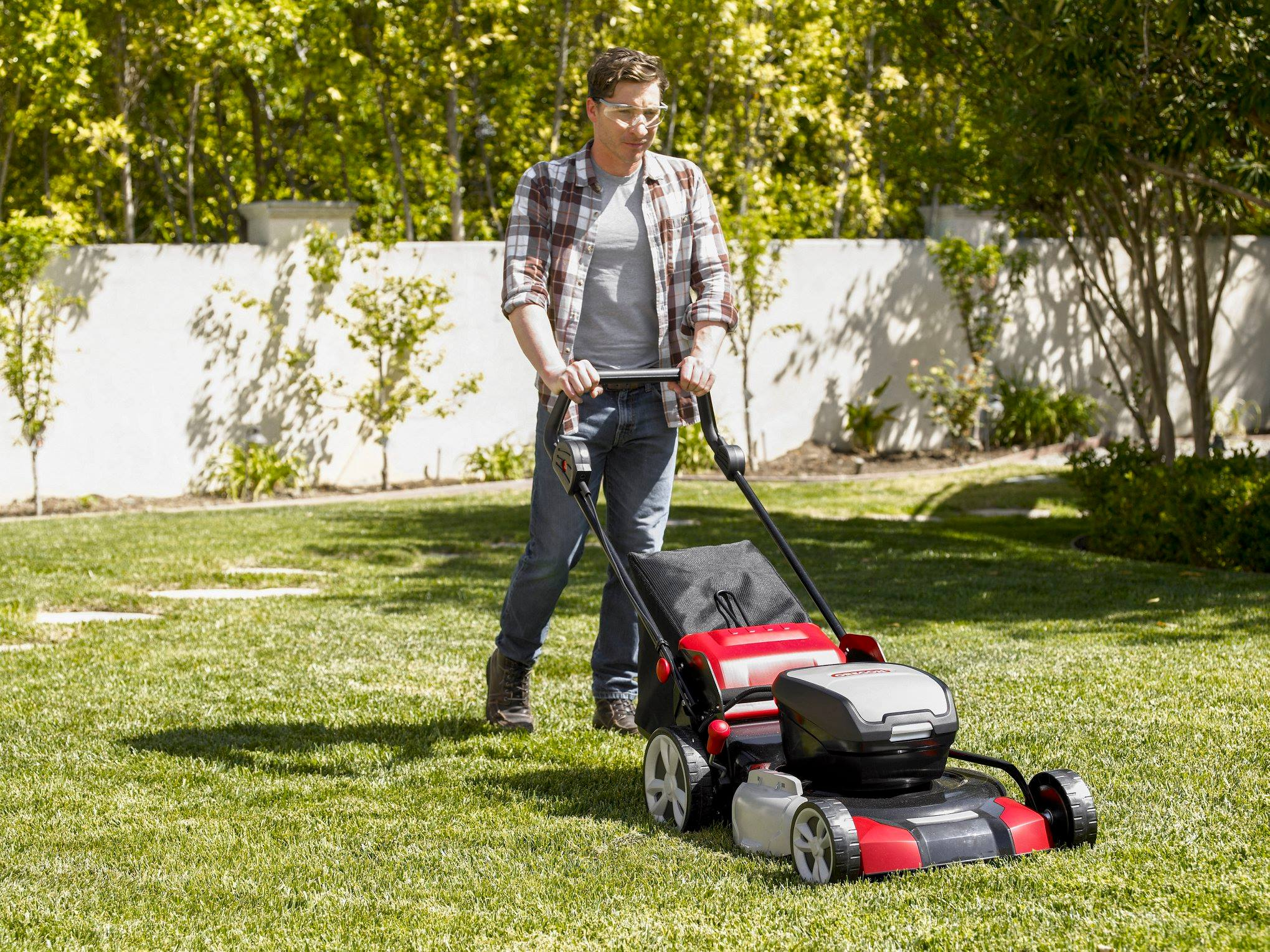 Man using a TORO walk behind mower to mow his lawn