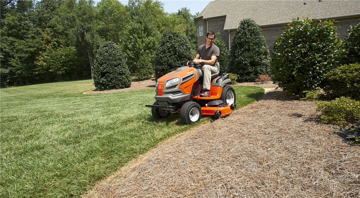 Man mows around the edge of a lawn on a Husqvarna riding lawn mower.