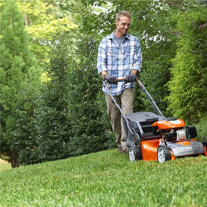 Man cuts the grass with a Husqvarna walk behind lawn mower.