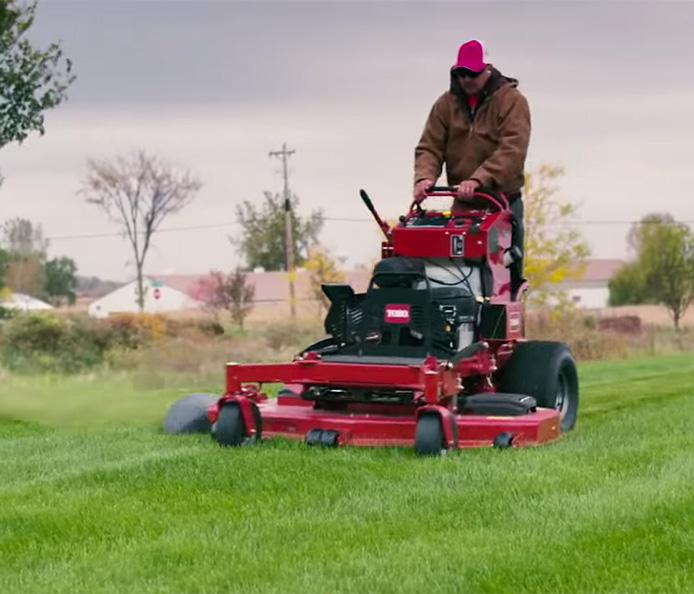 A man uses a Toro Grandstand® stand on mower in the early morning.