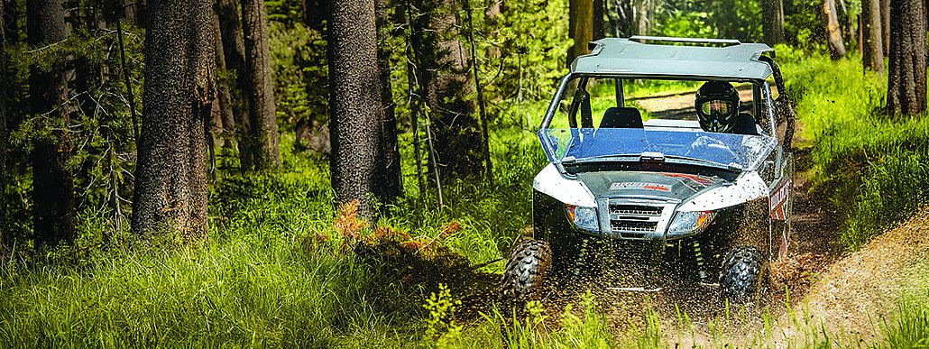 Textron SxS tearing up a trail through the woods