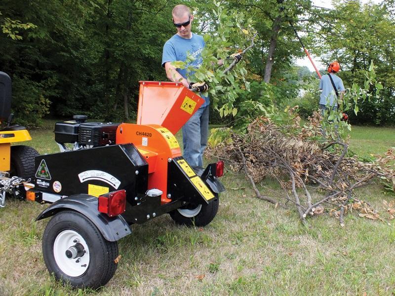 Landscaper shredding cut tree branches with an ECHO Bear Cat® CH4420 wood chipper