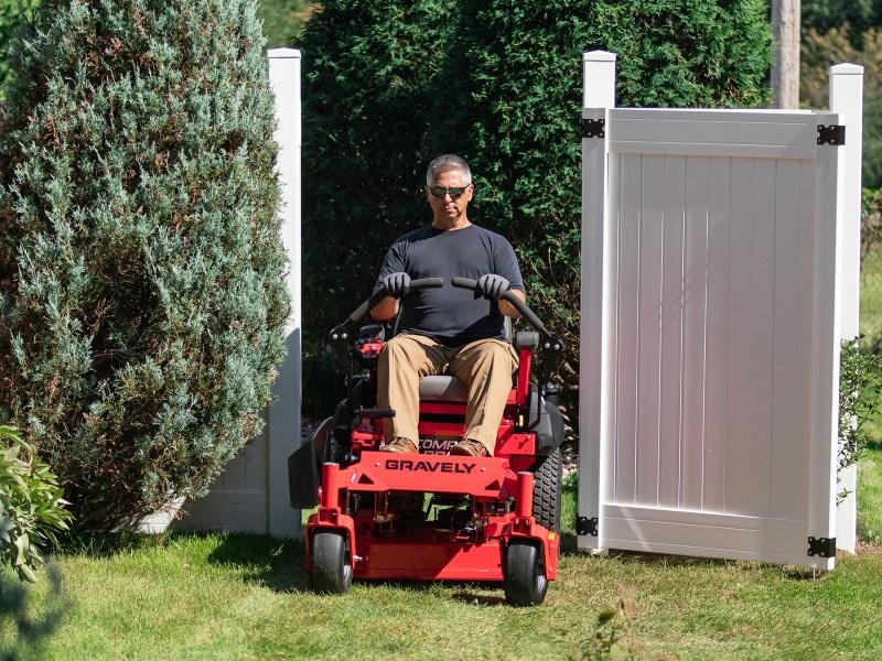 Man riding through narrow gate on a 2019 Gravely Compact-Pro® zero turn mower