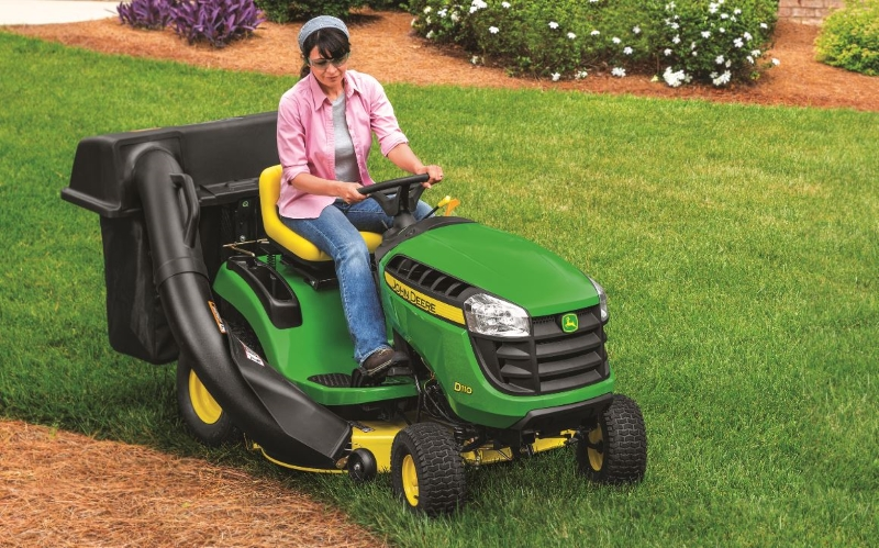 Lady Using John Deere Lawn Tractor with Debris Collection Attachment