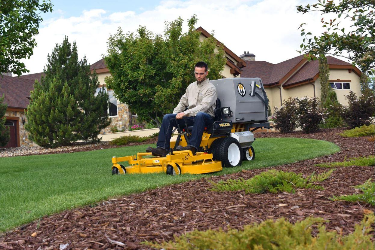 Man mowing lawn in residential neighborhood on 2019 Walker T25i