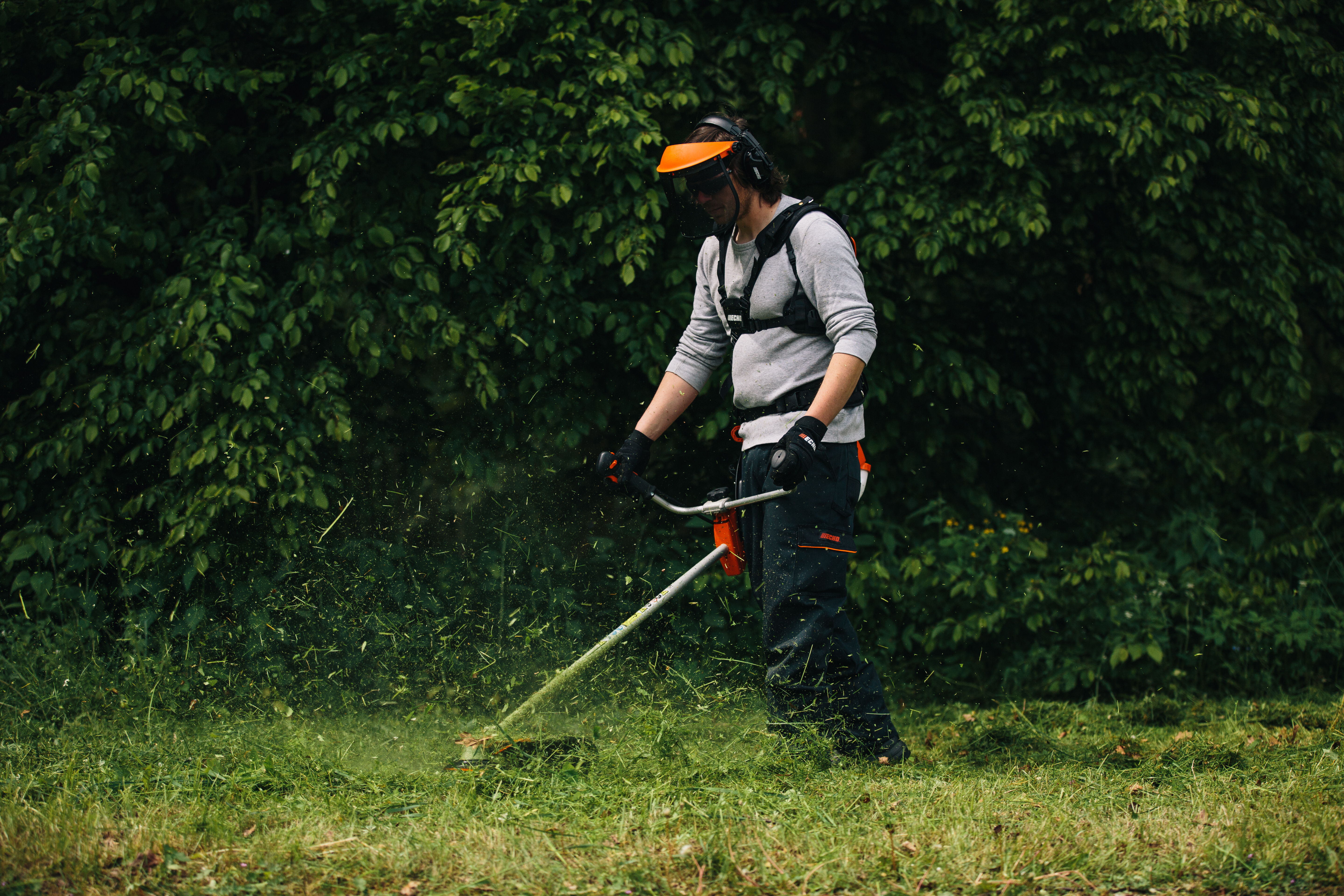 Man using a ECHO weedwhacker to take down high grass