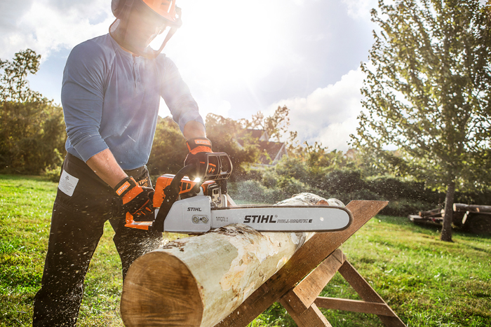 chainsaw being used by man to cut tree