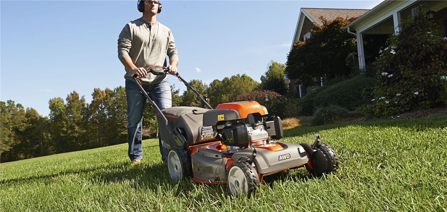 Man pushes a Husqvarna lawn mower in his yard wearing ear protection