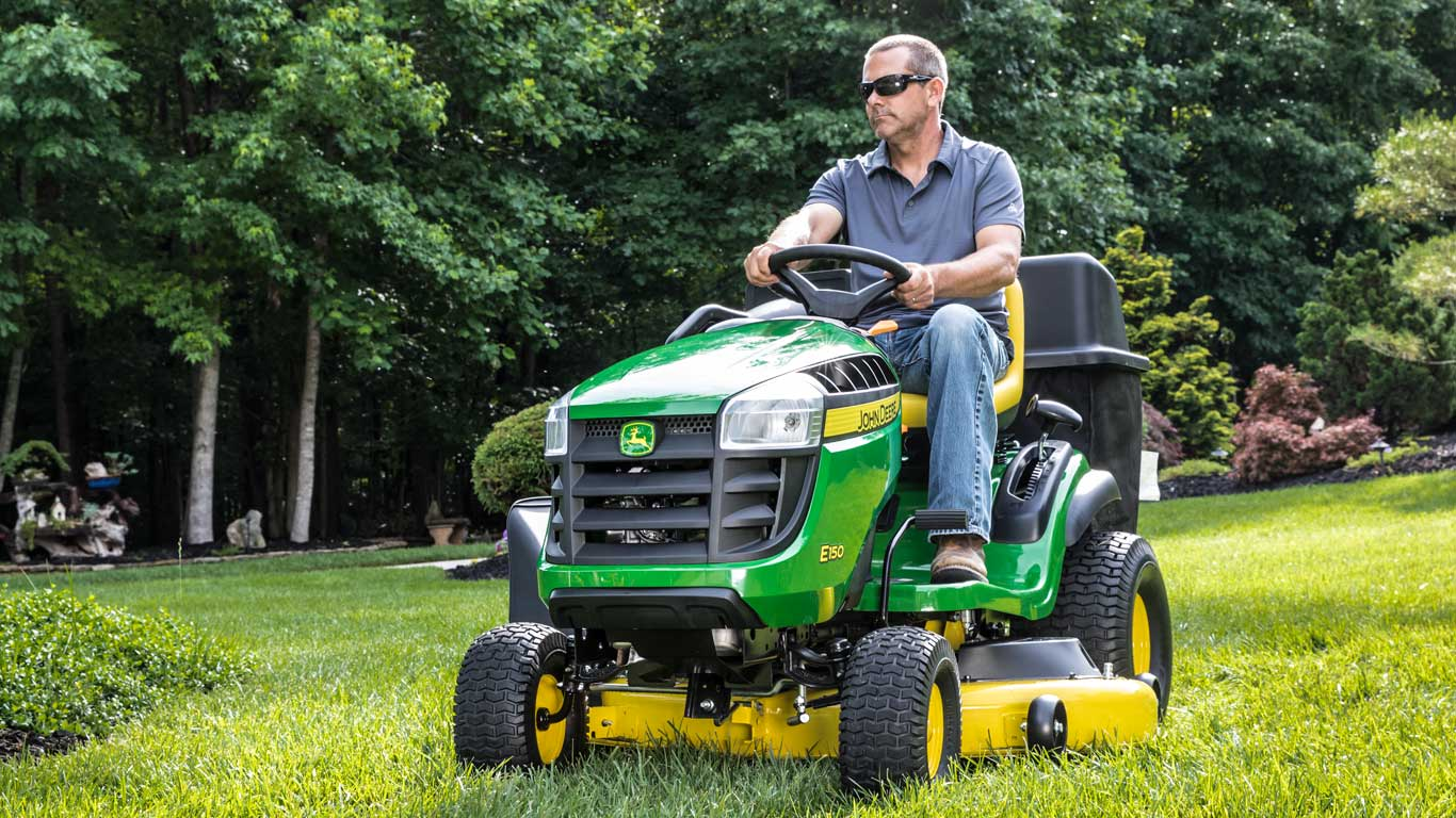 man riding John Deere lawn mower