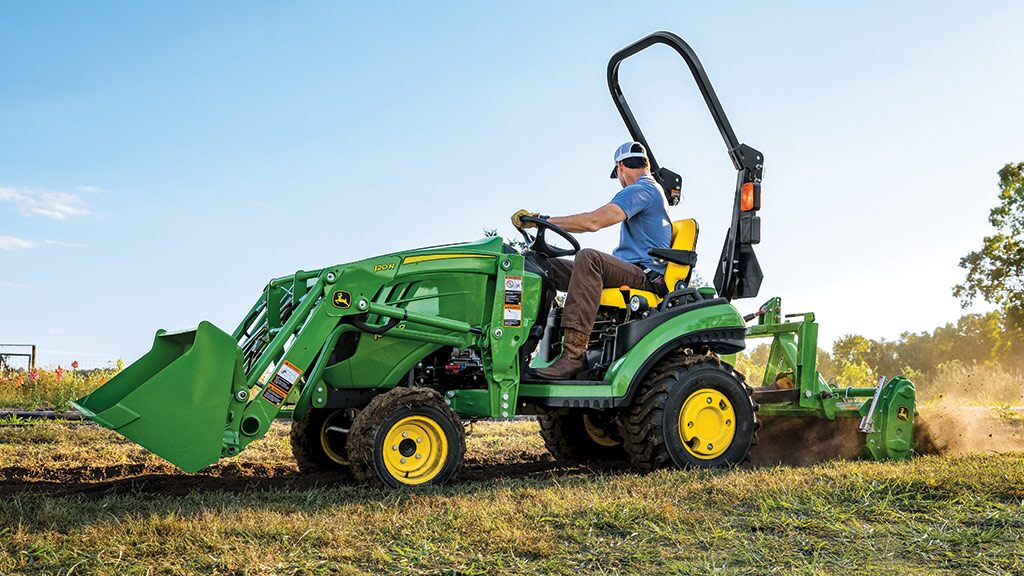 Man riding a John Deere Compact Tractor with a tiller
